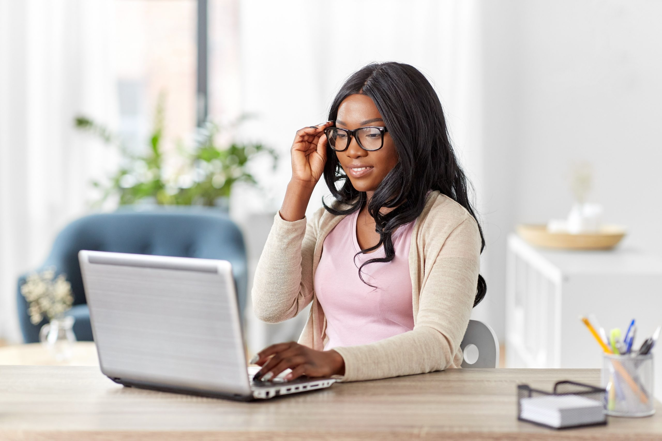 Young black woman with laptop working at home office to illustrate Home Office Furniture Ideas