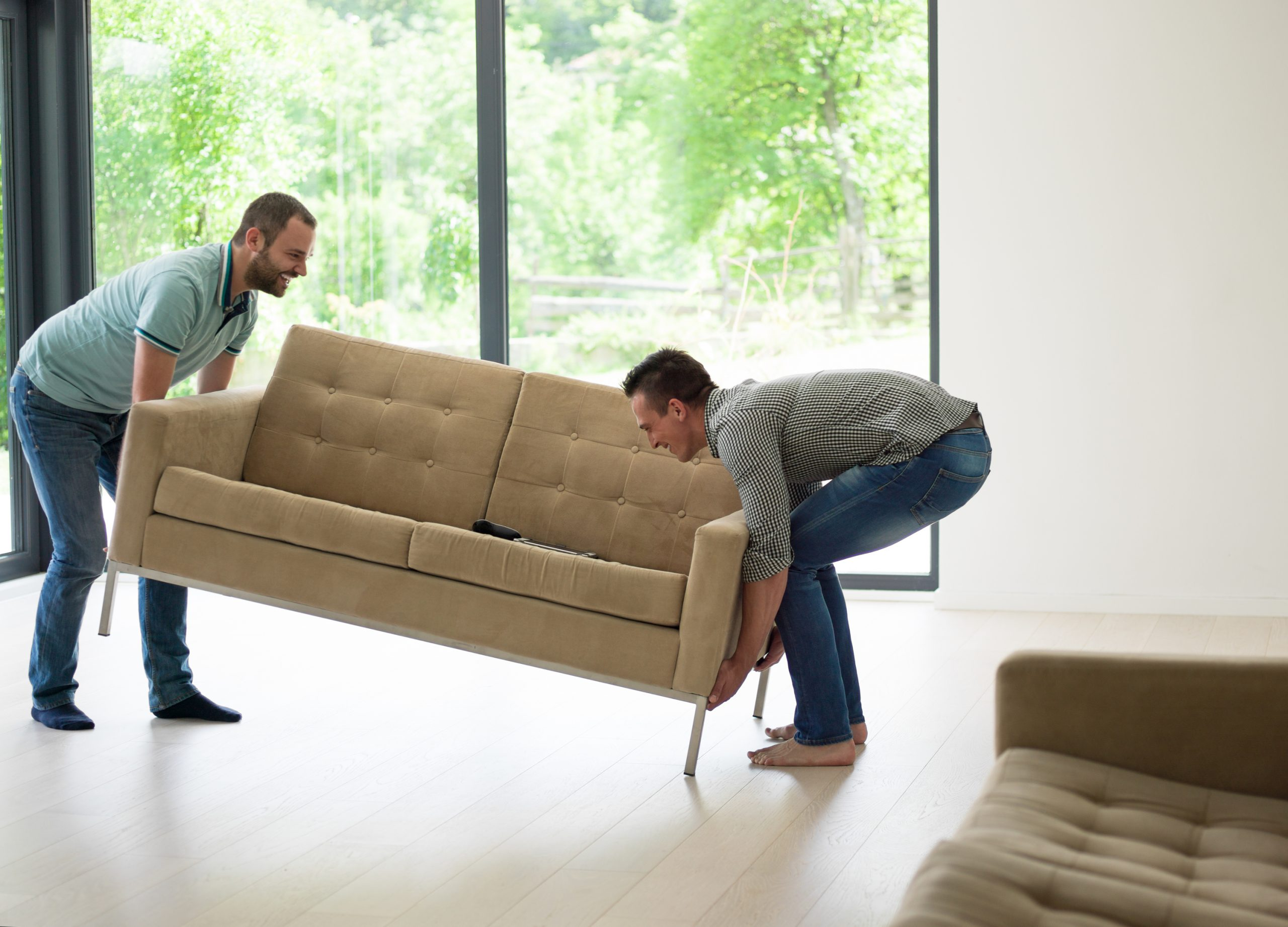 two young men carry the sofa in front of window to illustrate How To Measure For A Couch