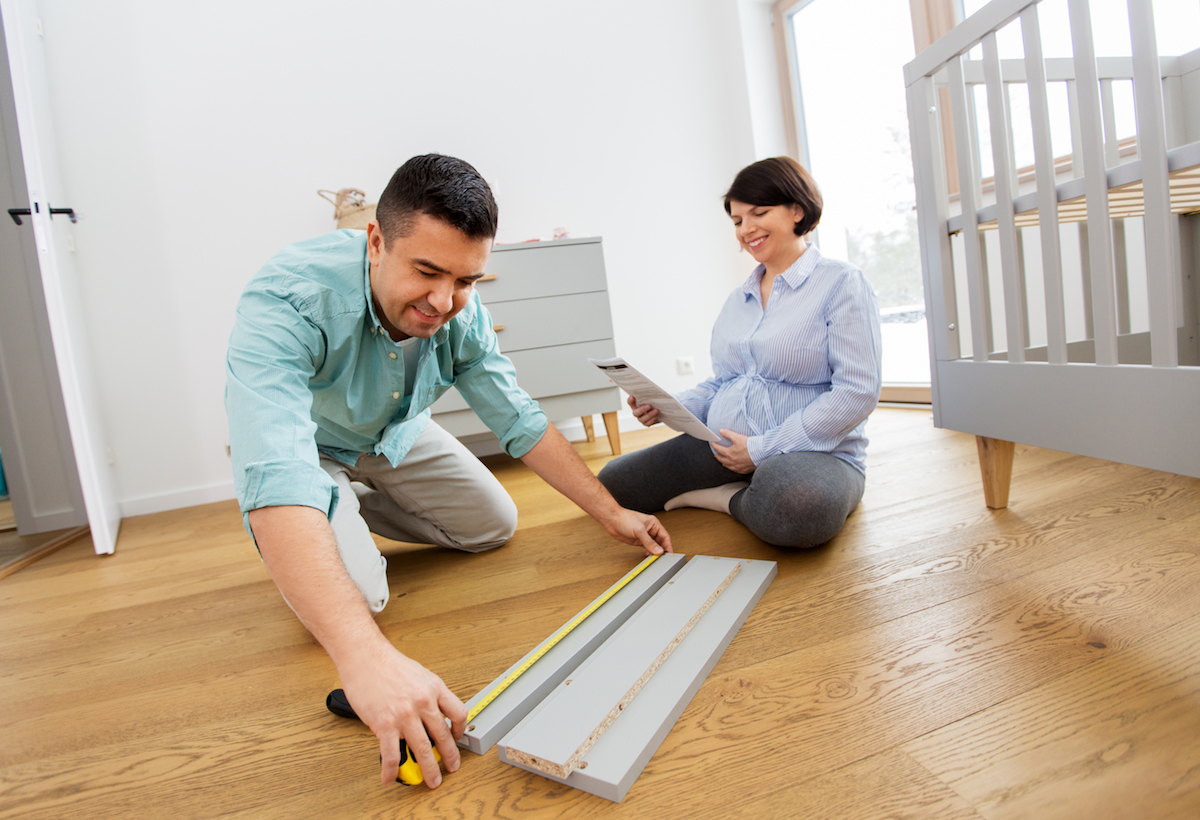 A couple measuring furniture for a baby's room